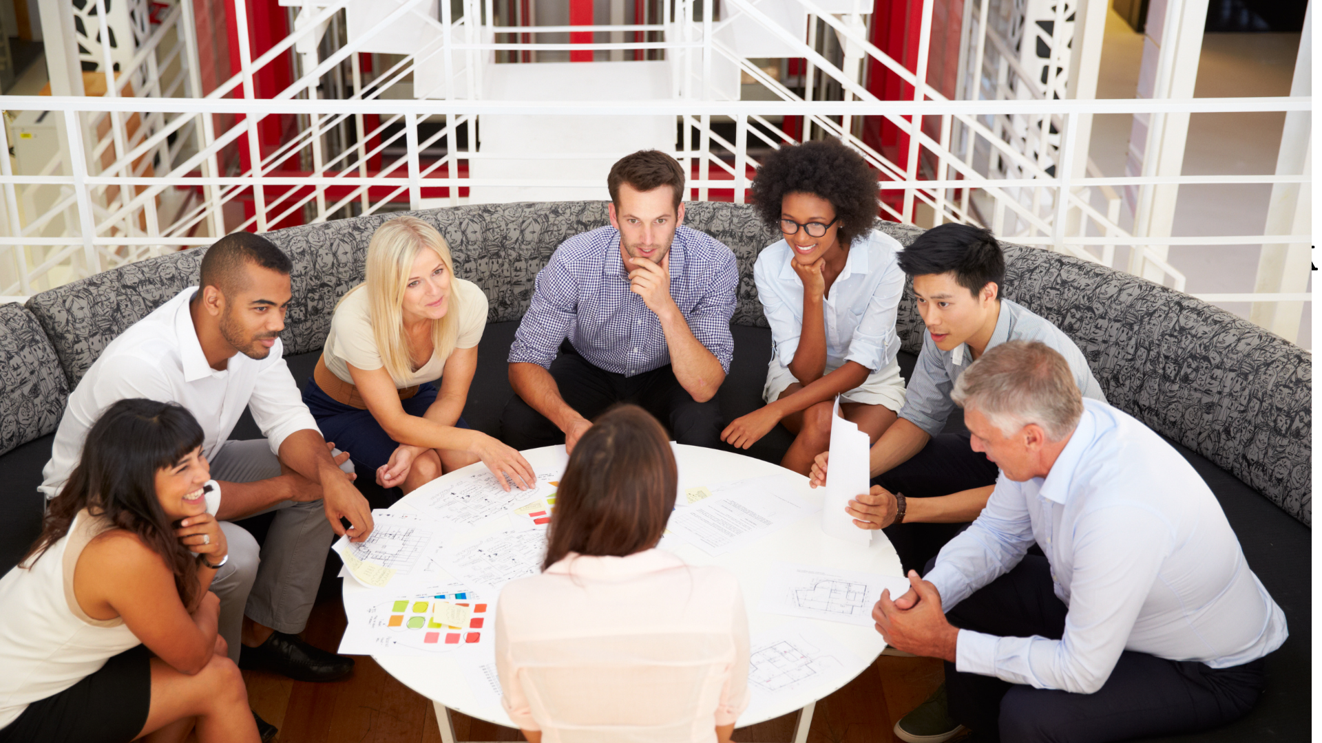 The image shows a group of adults sitting around a table listening intently to each other.